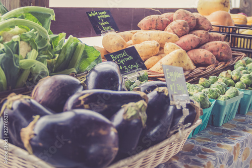 Fresh harvest vegetables attractively displayed in baskets at farmers market in vintage setting