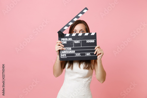 Valokuvatapetti Shocked bride woman in wedding dress hiding covering face with classic black film making clapperboard isolated on pastel pink background