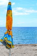 Beach umbrella near the water. Beach umbrella on the beach. Colorful holiday background. Bright colors on the beach.