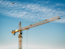 The Yellow Tower Crane On A Background Of Clouds