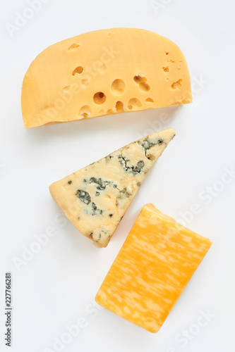 Different cheese types on light background. Maasdam cheese, french gorgonzola cheese and marble cheese. Delicious dairy products for gourmet.