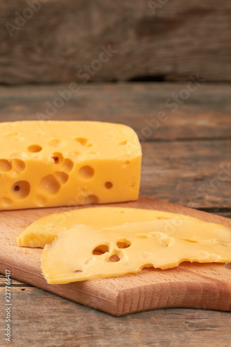 Slices of Maasdam cheese on cutting board. Fresh tasty swiss cheese on rustic wooden background.