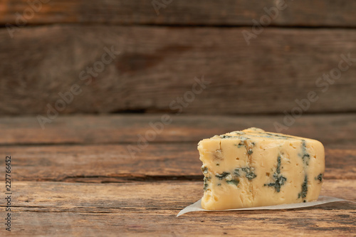 Blue cheese Gorgonzola on a rustic wooden background. French musty cheese and copy space. Tasty food for gourmet.