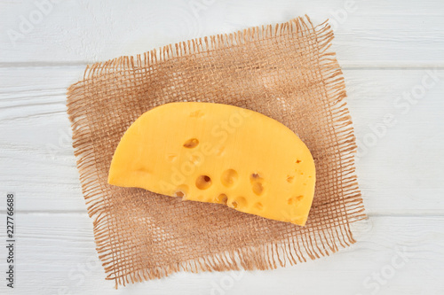Chunk of cheese on rustic napkin. Piece of Maasdam or Emmental cheese on white wooden table. Tasty milk ingredient.
