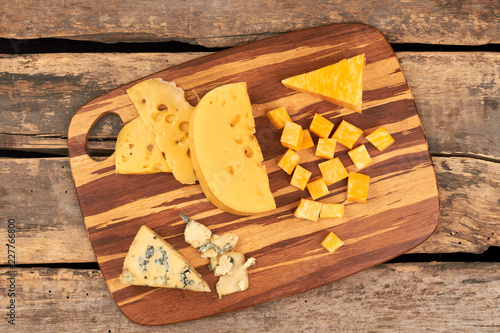 Assorted cheese on wooden board. Different sorts of cheese on rustic wooden background. Food for gourmet.