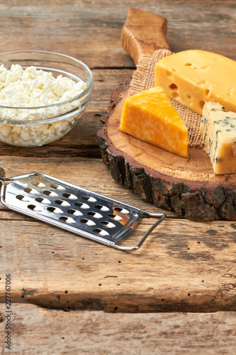 Variety of cheese on wooden background. Cottage cheese and hard cheese on rustic background. Delicious milk products.