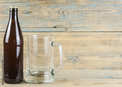 Tuinposter Bier / Cider Empty beer bottle and glass on grunge wooden background