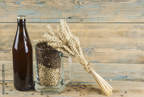 Tuinposter Bier / Cider Glass and bottle of beer, ears of barley on wooden background. Ale. horizontal with copy space