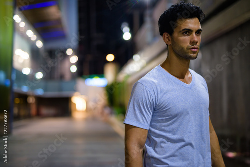 Fotografie, Obraz  Young handsome Hispanic man exploring the city streets at night