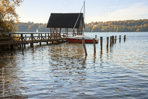 boathouse with jetty and sailing boat in the lake on a sunny autumn day, copy space