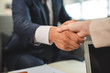 Close up of handshake of man and woman being business partners. Documents on blurred background