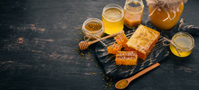 A Set Of Honey And Bee Products. Honey In Honeycomb. On A Black Wooden Background. Free Space For Text. Top View.