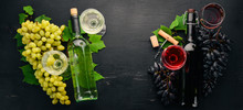 Set Of Red And White Wine In Bottles And Glasses. Grape. On A Black Wooden Background. Free Space For Text. Top View.