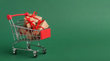 Shopping Cart With Craft Christmas Gifts Over Green Background