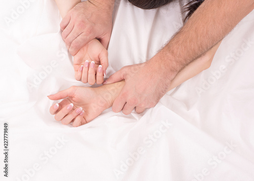 Photographie  Hands of couple who have sex on white crumpled sheet, focus on hands