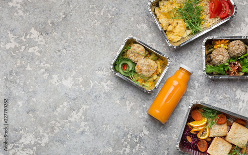 Foil containers with delicious food on gray background