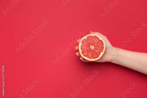 Woman holding cut grapefruit on red background