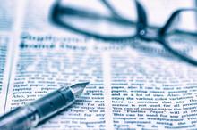 英字新聞と万年筆のあるビジネスイメージ
