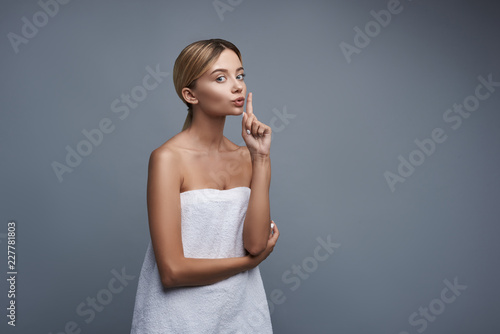 Poster Akt Lovely young lady looking pretty in her white towel and putting one finger to the lips while standing against the grey background