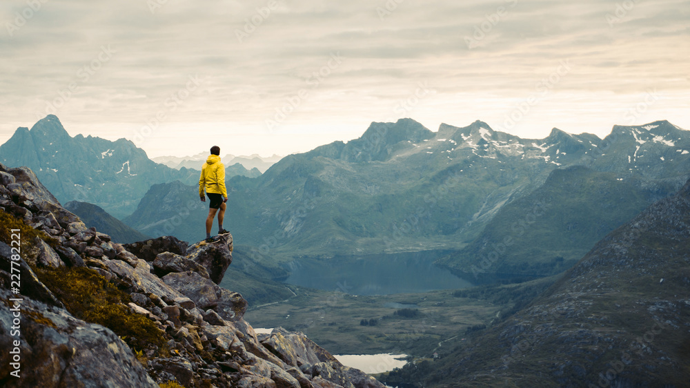 Fototapety, obrazy:  Adventurous man is standing on top of the mountain and enjoying the beautiful view during a vibrant sunset. Beautiful Nature Norway natural landscape aerial photography