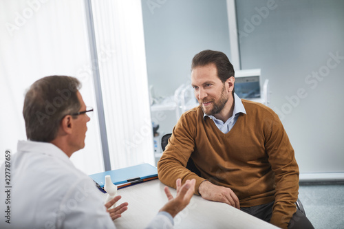 Fotografía  Male attentively listening to doctor, who explaining to him reasons for his anxi