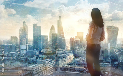 Foto  Young woman looking over the City of London at the early morning time