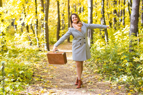 Photo Woman in a blue coat dancing in autumn park with suitcase