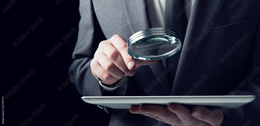 Fototapeta Businessman examines a tablet with a magnifying glass. Concept of internet security