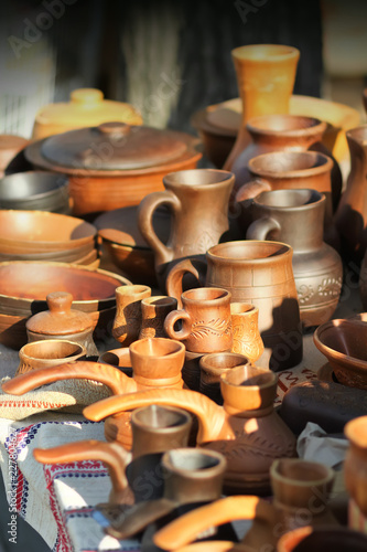 Traditional ukrainian cooking stove clay pots, mugs and jugs on market stall. Vintage style pottery
