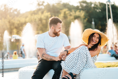 Photographie  Handsome bearded man and his beautiful girl resting near fountains