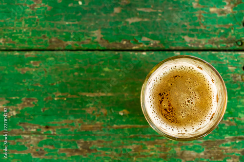 Canvas Prints Cafe A glass of beer with alcohol. Golden, intoxicating drink in a transparent mug, stands on a wooden stand in the rays of daylight. Top white and airy foam.