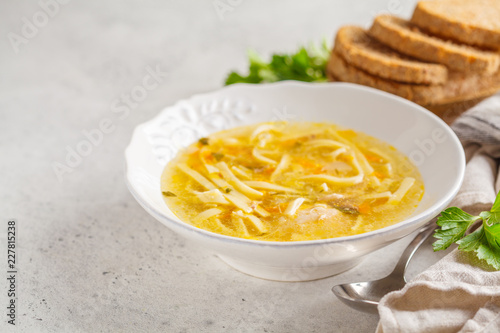 Homemade chicken noodle soup in a white plate, copy space.