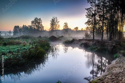 Staande foto Rivier Rzeka we mgle, tuż przed wschodem słońca. Ciepły blask w chmurach od pierwszych promieni słonecznych.