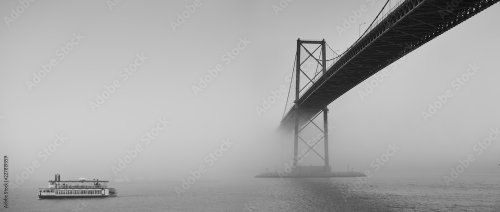 Fototapeta Ferry boat crossing under a suspension bridge in Halifax, Nova Scotia in thick fog.