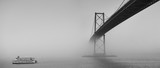 Fototapeta Most - Ferry boat crossing under a suspension bridge in Halifax, Nova Scotia in thick fog.