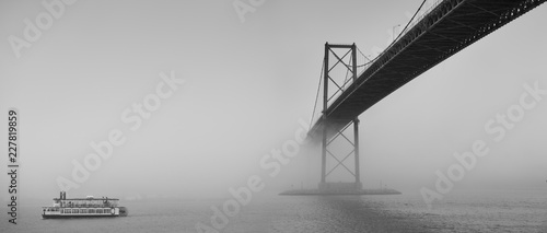 Spoed Fotobehang Bruggen Ferry boat crossing under a suspension bridge in Halifax, Nova Scotia in thick fog.