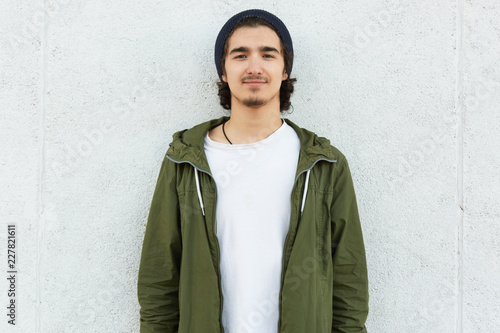 Photo Horizontal shot of stylish teenage boy wears black hat, white t shirt and green anorak, looks with satisfied expression direclty at camera, isolated over white background