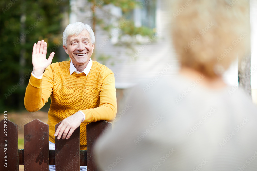 Fototapety, obrazy: Cheerful and friendly mature man waving hand to his neighbour while standing by fence