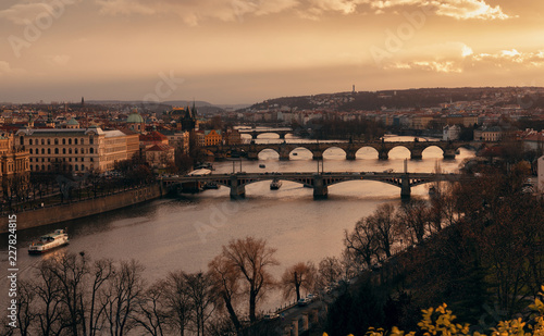 Poster Prague Beautiful panorama of Prague's skyline and some of its most famous landmarks, including Charles Bridge, during dramatic winter sunset