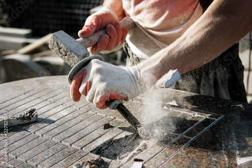 Photo Stone carver in gloves working with a hammer and chisel on a marble slab