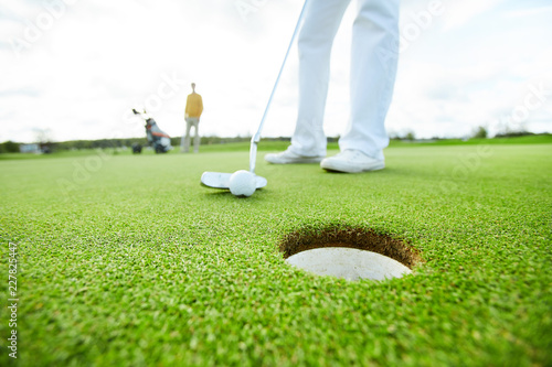 Poster Golf Golf player holding club close to the ball before hitting it while targeting at hole