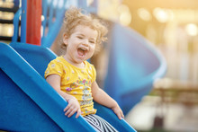 Little Toddler Playing At Playground Outdoors In Summer