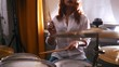 Repetition. Redhead girl plays on drums. Slow motion. Focus on drummer