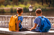 Kids after school, sitting on bench and talking. Education, back to school, friendship, childhood, communication and people concept