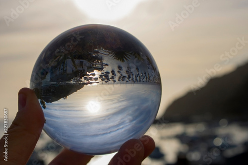 Photo  Sunrise through Clouds over Harbor and Ocean Captured in Glass Ball Reflection