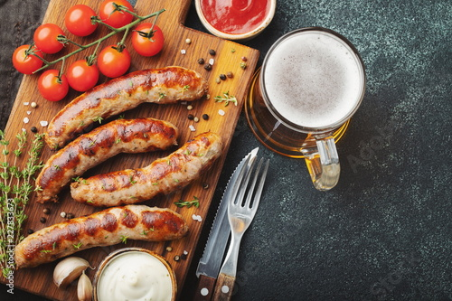 Fried sausages with sauces and herbs on a wooden serving Board Canvas Print