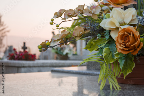 Fotografía Floral decoration on the grave with a cementary in the background