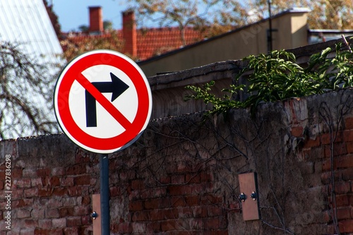 Obraz na płótnie The traffic sign prohibits turning right at the old brick wall.