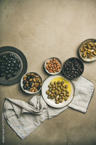 Flat-lay of various kinds of Mediterranean pickled olives in plates over grey concrete table background, top view, copy space, vertical composition. Mediterranean meze appetizer
