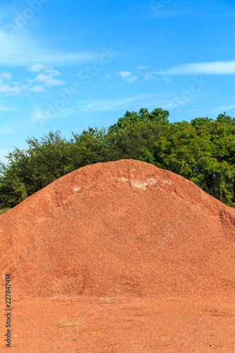 Poster Koraal Bin of Red Clay Chips Fine Coarseness: Bin of fine coarse red clay chips used for landscaping and driveways on display and for sale.